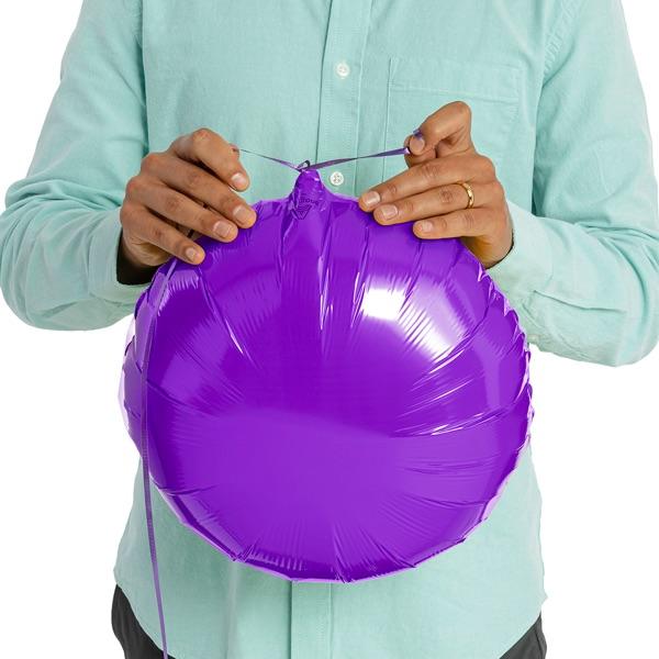 Hands tying ribbon on foil balloon