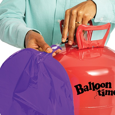 Hands inflating foil balloon